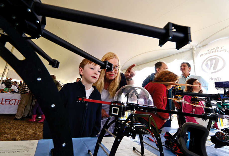 Hour photo / Erik Trautmann Leslie Flinn and her son Grady check out Quadframe UAVs at the annual Mini Makers Faire at the Jessup Green in Westport Saturday