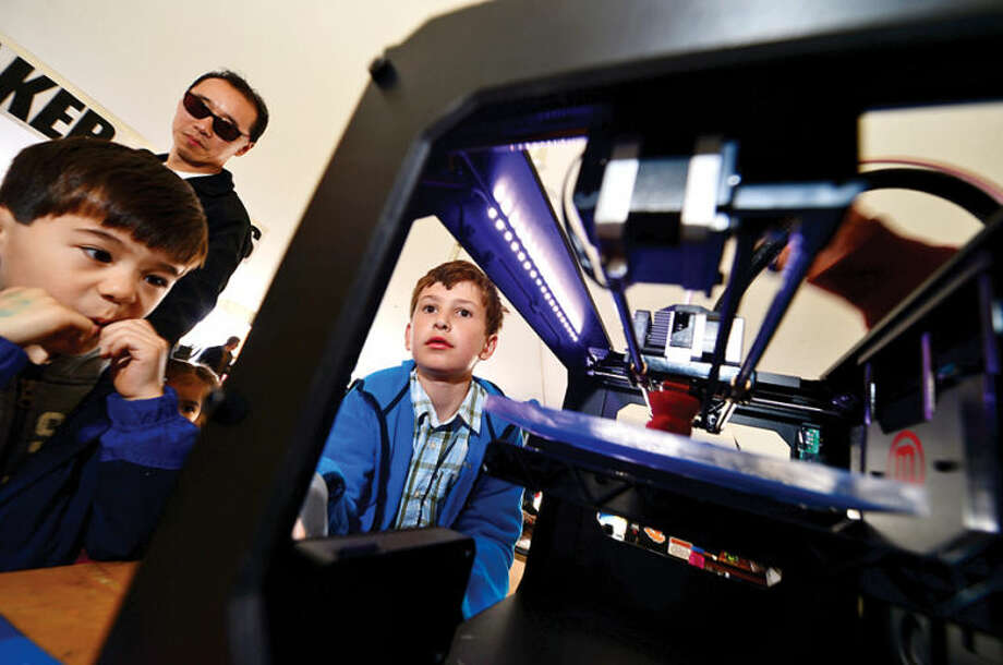 Hour photo / Erik Trautmann Connor Yuan, 5, and Jeffrey Pogue, 9, check out a Maker Bot 3-d printer during the annual Mini Makers Faire at the Jessup Green in Westport Saturday.