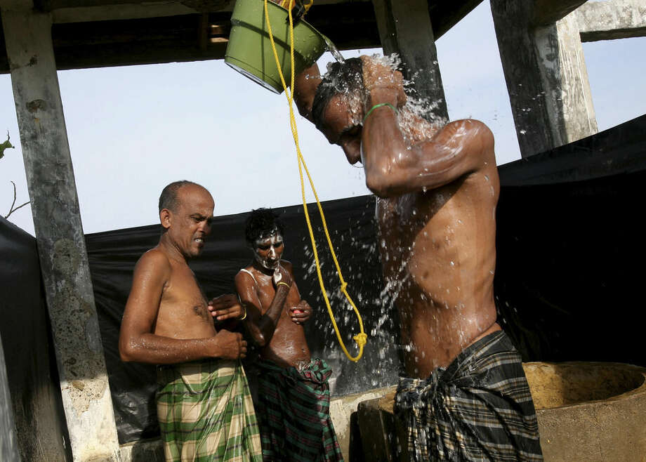 Bangladeshi migrants take showers at a temporary shelter in Lapang, Aceh province, Indonesia, Thursday, May 14, 2015. More than 1,600 migrants, including Rohingya Muslims from Myanmar, have landed on the shores of Malaysia and Indonesia in the past week and thousands more are believed to have been abandoned at sea, floating on boats with little or no food after traffickers literally jumped ship fearing a crackdown. (AP Photo/Binsar Bakkara)