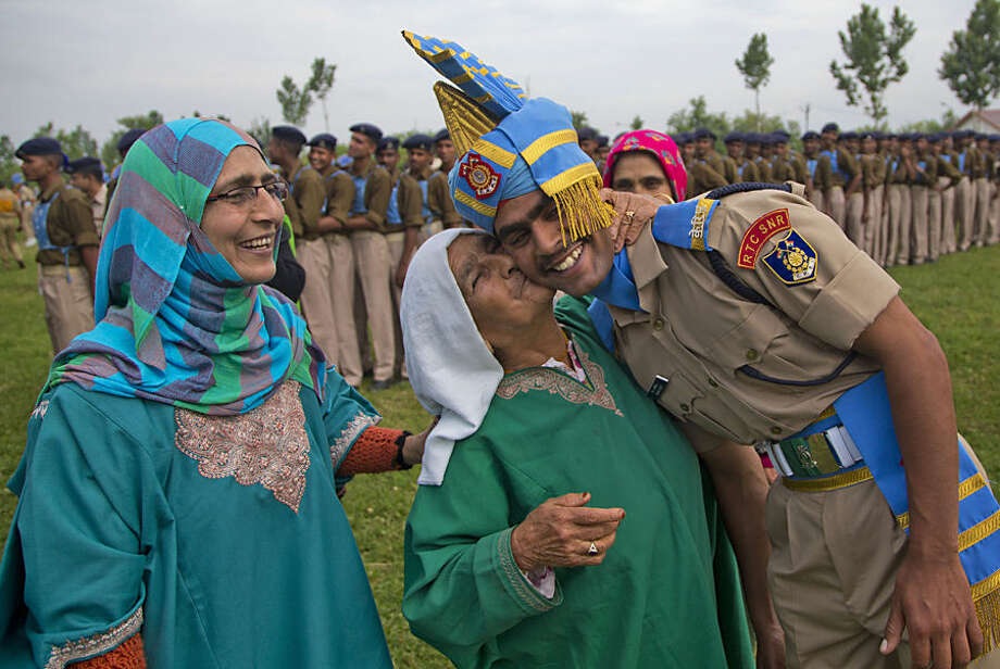 A woman kisses the forehead of her grandson after he was inducted as a soldier of the Indian Central Reserve Police Force (CRPF) at a base camp on the outskirts of Srinagar, Indian controlled Kashmir, Thursday, May 14, 2015. More than three hundred new CRPF soldiers will join the Indian security men fighting separatist Islamic guerrillas in Kashmir and Maoist rebels in different parts of India.(AP Photo/Dar Yasin)