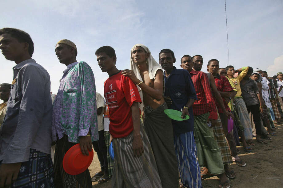 Ethnic Rohingya men queue up for breakfast at a temporary shelter in Lapang, Aceh province, Indonesia, Thursday, May 14, 2015. More than 1,600 migrants and refugees from Myanmar and Bangladesh have landed on the shores of Malaysia and Indonesia in the past week and thousands more are believed to have been abandoned at sea, floating on boats with little or no food after traffickers literally jumped ship fearing a crackdown. (AP Photo/Binsar Bakkara)
