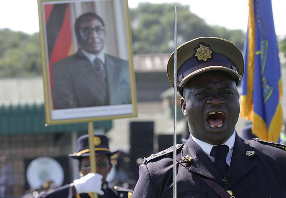 A police officer shouts orders during the Presidential Graduation ceremony which was attended by President Robert Mugabe, pictured in poster in the background, at the General Police headquarters, in Harare, Zimbabwe, Thursday, May 14, 2015. A total of 698 police officers graduated at the ceremony after undergoing training by the Zimbabwe Republic police. (AP Photo/Tsvangirayi Mukwazhi)