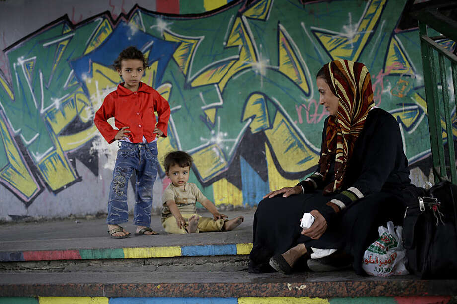An Egyptian woman sells tissue as she sits next to her daughter Yara, 5, and her son Youssef, 16 months, under a bridge in Cairo, Egypt, Thursday, May 14, 2015. (AP Photo/Hassan Ammar)