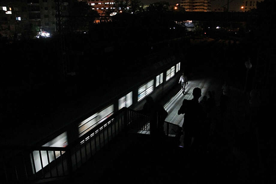 In this Aug. 19, 2014 photo, people make their way at the Maadi metro station during an electricity outage, in Cairo, Egypt. The Cairo Metro system sprawls across the city, delivering an estimated 3.6 million passengers per day over three different lines and approximately 78 kilometers (49 miles) of train track, both above ground and below the city center. (AP Photo/Heba Elkholy)