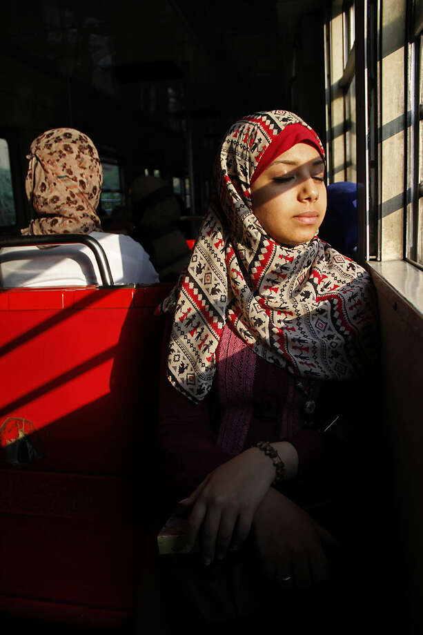 In this June 8, 2014 photo, Leila Abdel Basset, 24, rides the metro to work in an all-female car, in Cairo, Egypt. The cars are not air-conditioned, which can make conditions truly miserable on a crowded summer day. Savvy passengers know to avoid the morning and evening rush hours, when the cars can become packed to maximum density with commuting civil servants and rowdy students. (AP Photo/Heba Elkholy)