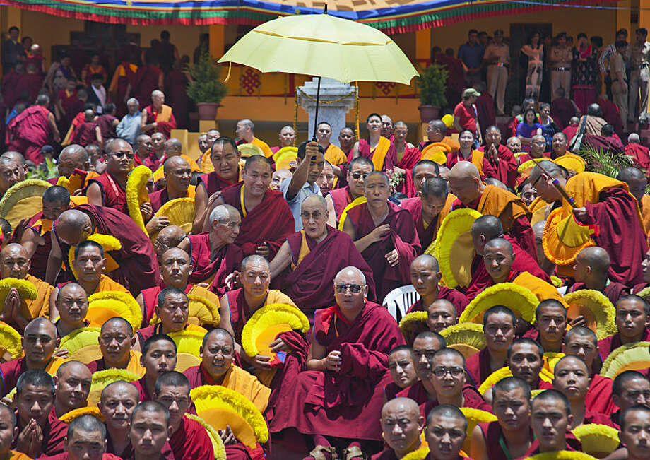An aide holds an umbrella as Tibetan spiritual leader the Dalai Lama, center, sits for a group photo with monks after giving a religious talk at the Gyuto Monastery in Dharmsala, India, Wednesday, May 13, 2015. The four-day talk by the Tibetan leader ended Wednesday. (AP Photo/Ashwini Bhatia)