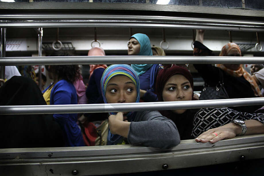 In this Sept. 13, 2014 photo, Egyptian women look from an all-female car at the Shohadaa (Martyrs) metro station in Cairo, Egypt. Before the 2011 Egyptian revolution the station was named for former President Hosni Mubarak. In a city known, as much as anything, for its dysfunction, the Cairo Metro stands as a singular achievement. It's reliable, well-maintained and relatively clean. (AP Photo/Heba Elkholy)