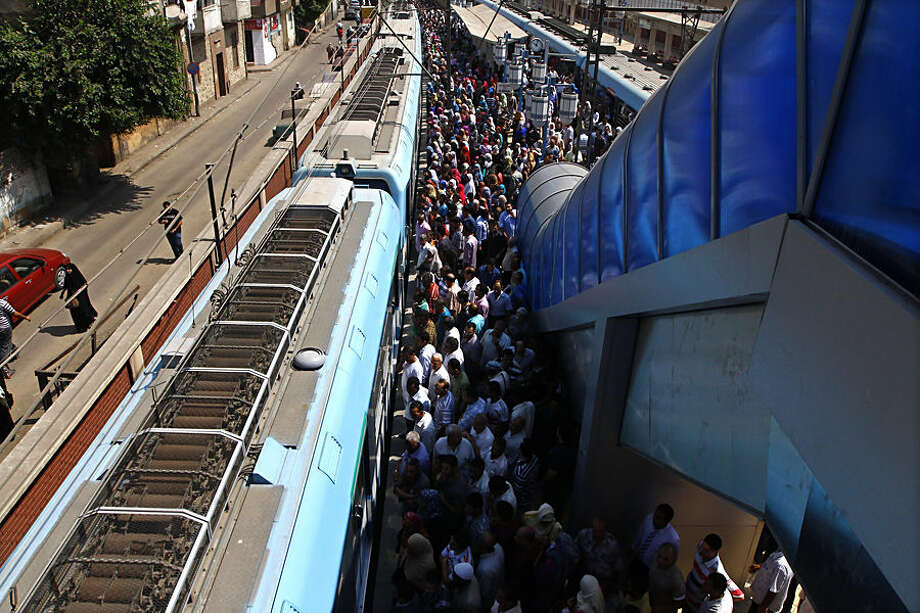 In this July 11, 2012 photo, Egyptians wait to board at the El Sayeda Zeinab metro station in Cairo, Egypt. The Cairo Metro system sprawls across the city, delivering an estimated 3.6 million passengers per day over three different lines and approximately 78 kilometers (49 miles) of train track, both above ground and below the city center. (AP Photo/Heba Elkholy)