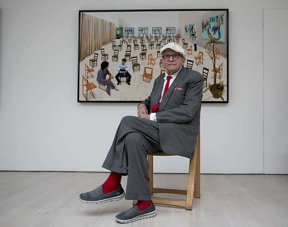 "British artist David Hockney poses for photographers in front of his photographic drawing printed on paper ""The Chairs"" which features as part of the ""David Hockney Painting and Photography"" exhibition at the Annely Juda Fine Art gallery in London, Thursday, May 14, 2015. The show, which runs from May 15 to June 27, is an exploration of Hockney's interest in perspective and features a series of portraits, including his American friends playing cards, and other scenes painted in his Los Angeles studio in 2014 and 2015. (AP Photo/Matt Dunham)"