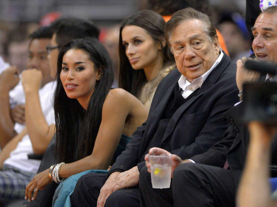 """In this photo taken on Friday, Oct. 25, 2013, Los Angeles Clippers owner Donald Sterling, right, and V. Stiviano, left, watch the Clippers play the Sacramento Kings during the first half of an NBA basketball game in Los Angeles. The NBA is investigating a report of an audio recording in which a man purported to be Sterling makes racist remarks while speaking to his Stiviano. NBA spokesman Mike Bass said in a statement Saturday, April 26, 2014, that the league is in the process of authenticating the validity of the recording posted on TMZ's website. Bass called the comments """"disturbing and offensive."""" (AP Photo/Mark J. Terrill)"""