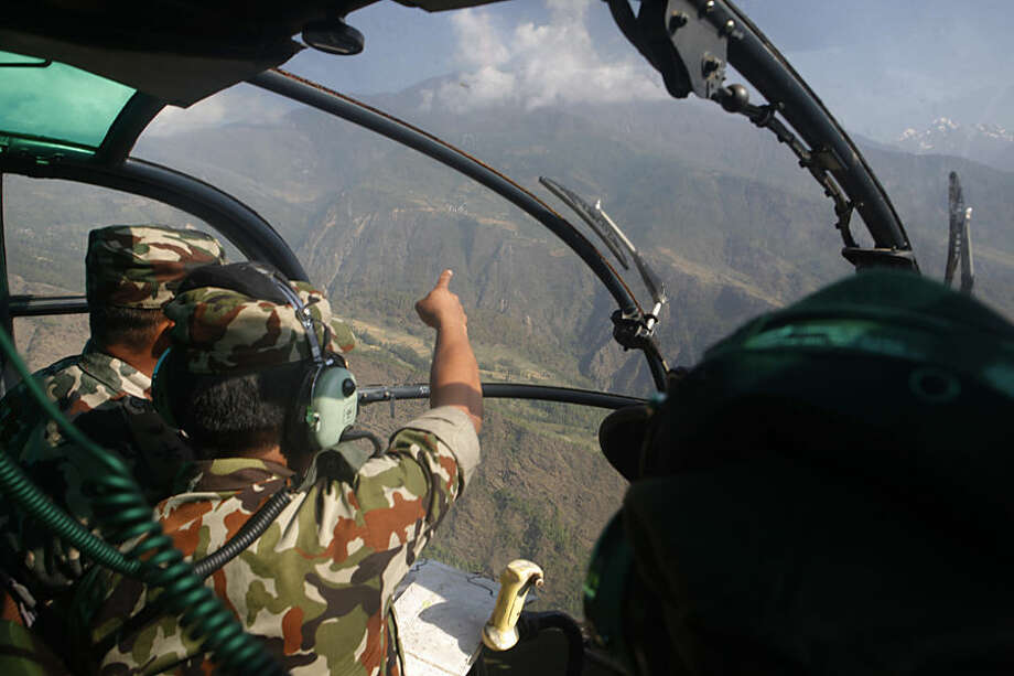 Nepalese army men search for the missing U.S. Marine helicopter in the earthquake affected Dolakha District, Nepal, Thursday, May 14, 2015. The helicopter carrying six Marines and two Nepalese soldiers disappeared Tuesday while delivering aid in the country's northeast, U.S. officials said. (AP Photo/Niranjan Shrestha)