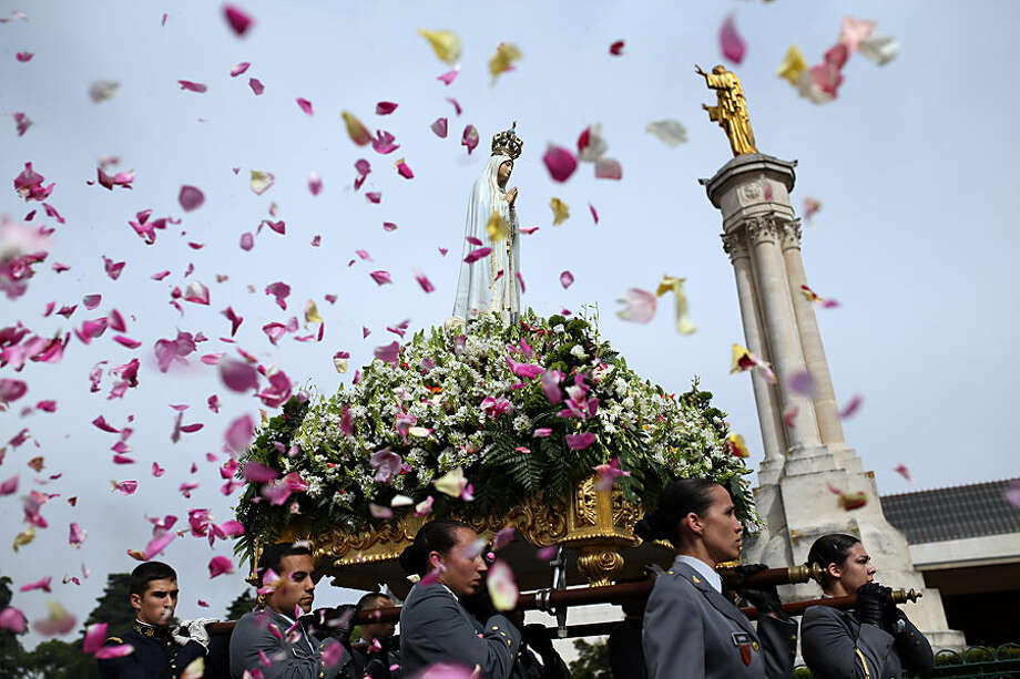 Worshipper throw flower petals at the statue of the Our Lady of Fatima as it is carried at the Our Lady of Fatima shrine, in Fatima, central Portugal, Wednesday, May 13, 2015. Every year on May 12 and 13 tens of thousands of Catholic believers go on pilgrimage to the Fatima sanctuary to pray and attend masses where the apparitions of the Virgin Mary were witnessed by three shepherd children Lucia, Jacinta and Francisco in 1917. (AP Photo/Francisco Seco)