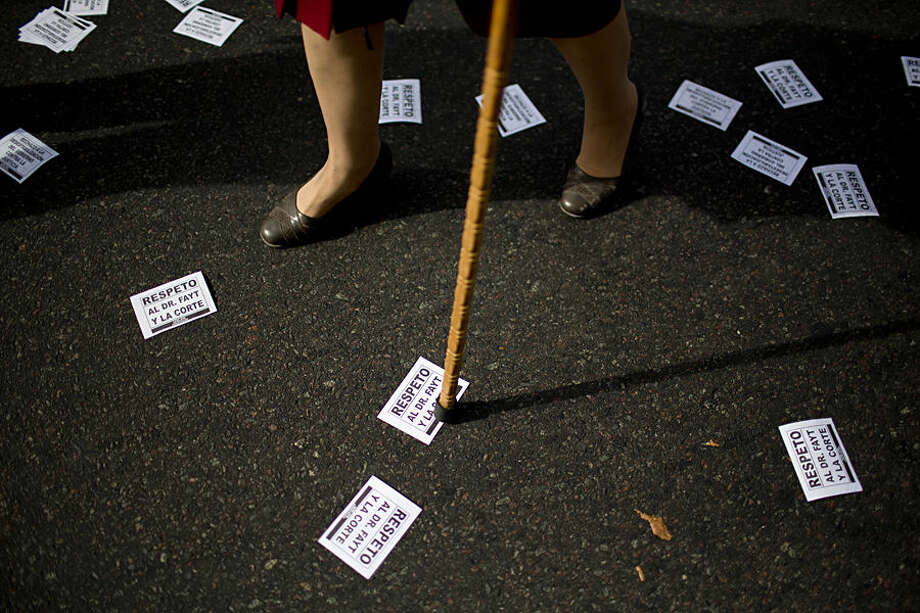 """A woman using a walking cane passes through a street full of leaflets that read in Spanish """"Respect for Fayt and the court"""" during a rally in support of Supreme Court Judge Carlos Fayt in Buenos Aires, Argentina, Wednesday, May 13, 2015. The government is questioning whether the 97-year-old judge is in good enough physical and mental condition to stay on the court, after he didn't attend a court meeting that re-elected the head of the court. His fellow court members gave him their support Wednesday, saying he cast his vote and that those decisions can be signed inside or outside the court. (AP Photo/Natacha Pisarenko)"""