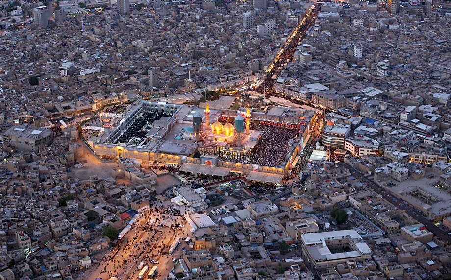 In this aerial view of the holy Muslim Shiite shrine of Imam Moussa al-Kazim, pilgrims gather to commemorate his death, in the Shiite district of Kazimiyah, Baghdad, Iraq, Wednesday, May 13, 2015. The anniversary of 8th century Shiite Imam Moussa al- Kazim drew tens of thousands of Shiites from all walks to converge on his golden-domed shrine in northern Baghdad. The pilgrims typically march to the shrine while hundreds of tents are erected to offer them free food, drinks and services. (AP Photo/Hadi Mizban)
