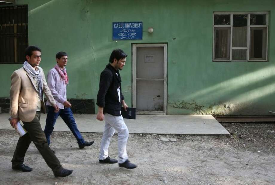 "Afghan university students walk in front of health clinic at Kabul University where slain American Jon Gabel worked at Kabul University, teaching computer science classes in his spare time, in Kabul, Afghanistan, Saturday, April 26, 2014. On Saturday, Kabul University vice chancellor Mohammad Hadi Hadayati identified the other two Americans killed in the attack as health clinic administrator Jon Gabel and his visiting father, Gary, also from the Chicago area. Jon Gabel's wife, also an American, was wounded, Hadayati said. ""We have lost a great man, a great teacher, a man who was here only to serve the Afghan people,"" Hadayati said. Jon Gabel worked for the U.S.-based charity Morning Star Development and ran a health clinic at Kabul University, teaching computer science classes in his spare time, Hadayati said. Jon Gabel's parents were visiting from Chicago, and Hadayati had lunch with the whole family the day before the attack. (AP photo/Rahmat Gul)"