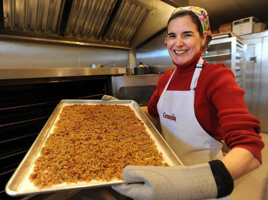 Jen Olbrys, of Stratford, removes a tray of her Granola by Jen from the oven in her rented commercial kitchen in Stratford on Wednesday. Olbrys sells her product in twelve ounce bags at farmers markets, online, and in select stores. (Photo: Brian A. Pounds / Hearst Connecticut Media)
