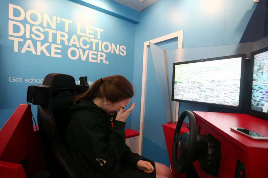 Trinity Catholic sophomore Grace Curley-Holmes, 16, puts her head in her hand after accidentally driving over a pedestrian in the distracted driving training simulator parked outside of Trinity Catholic on Thursday, May 5, 2016. (Photo: Michael Cummo / Hearst Connecticut Media)