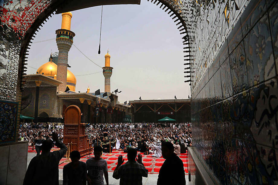 Shiite pilgrims pray at the Imam Mousa al-Kazim shrine to commemorate his death, in the Shiite district of Kazimiyah, Baghdad, Iraq, Wednesday, May 13, 2015. The anniversary of 8th century Shiite Imam Moussa al-Kazim drews tens of thousands of Shiites from all walks to converge on his golden-domed shrine in northern Baghdad. The pilgrims typically march to the shrine while hundreds of tents are erected to offer them free food, drinks and services. (AP Photo/Karim Kadim)