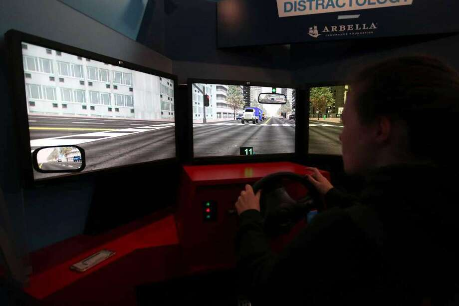 Trinity Catholic sophomore Grace Curley-Holmes, 16, drives the distracted driving training simulator, which gives new drivers various road scenarios to drive through, on Thursday, May 5, 2016. The simulation mobile is parked outside of Trinity Catholic to allow new drivers to test their knowledge of the rules of the road. (Photo: Michael Cummo / Hearst Connecticut Media)