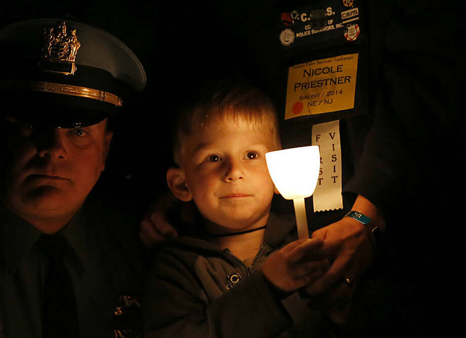 Brian Priestner holds a candle and his mother's hand during the National Law Enforcement Officers Memorial Fund's Annual Candlelight Vigil, Wednesday, May 13, 2015 in Washington. Brian's uncle, Waldwick, N.J., Officer Christopher Goodell, died in the line of duty. (AP Photo/Alex Brandon)