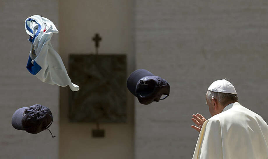 Faithful throw in the air a jersey and two hats as Pope Francis leaves at the end of his weekly general audience in St. Peter's Square at the Vatican, Wednesday, May 13, 2015. (AP Photo/Alessandra Tarantino)