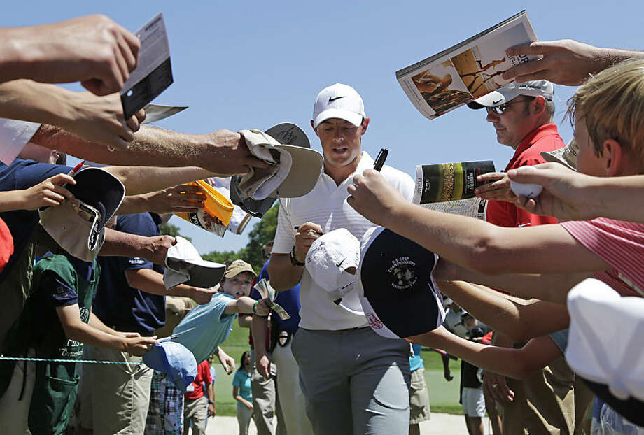 Rory McIlroy signs autographs as he walks to the third tee during the pro-am for the Wells Fargo Championship golf tournament at the Quail Hollow Club in Charlotte, N.C., Wednesday, May 13, 2015. (AP Photo/Chuck Burton)