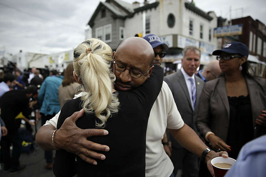Philadelphia Mayor Michael Nutter, center right, hugs Lori Dee Patterson, a nearby resident, after she handed him a cup of coffee after he spoke at a news conference near the scene of a deadly train derailment, Wednesday, May 13, 2015, in Philadelphia. An Amtrak train headed to New York City derailed and crashed in Philadelphia on Tuesday night, killing at least six people and injuring dozens more. (AP Photo/Matt Slocum)