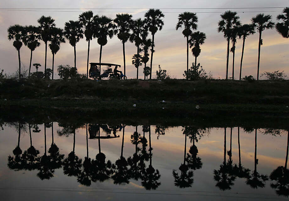 A man drives a motor cart at dawn as he takes passengers into town from the outskirts of Phnom Penh, Cambodia, Thursday morning, May 14, 2015. Motorcycle-based transportation continues to be popular in the developing nation due to their relative low cost and fuel-efficiency despite the increase in automobile use in recent years. (AP Photo/Heng Sinith)