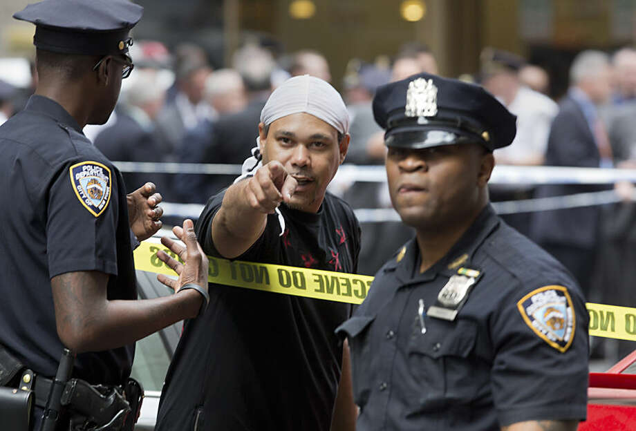 A witness talks with police at a Manhattan crime scene, Wednesday, May 13, 2015, in New York, after a man apparently wielding a hammer was shot and wounded by police. The shooting took place shortly after 10 a.m., blocks from Madison Square Garden and Penn Station. (AP Photo/Mark Lennihan)