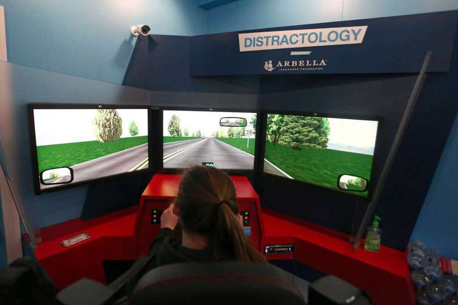 Trinity Catholic sophomore Grace Curley-Holmes, 16, drives the distracted driving training simulator parked outside of the school on Thursday, May 5, 2016. The simulator uses three screens, to give the driver a full view of perpendicular streets and oncoming traffic, as if they were in a real car. (Photo: Michael Cummo / Hearst Connecticut Media)