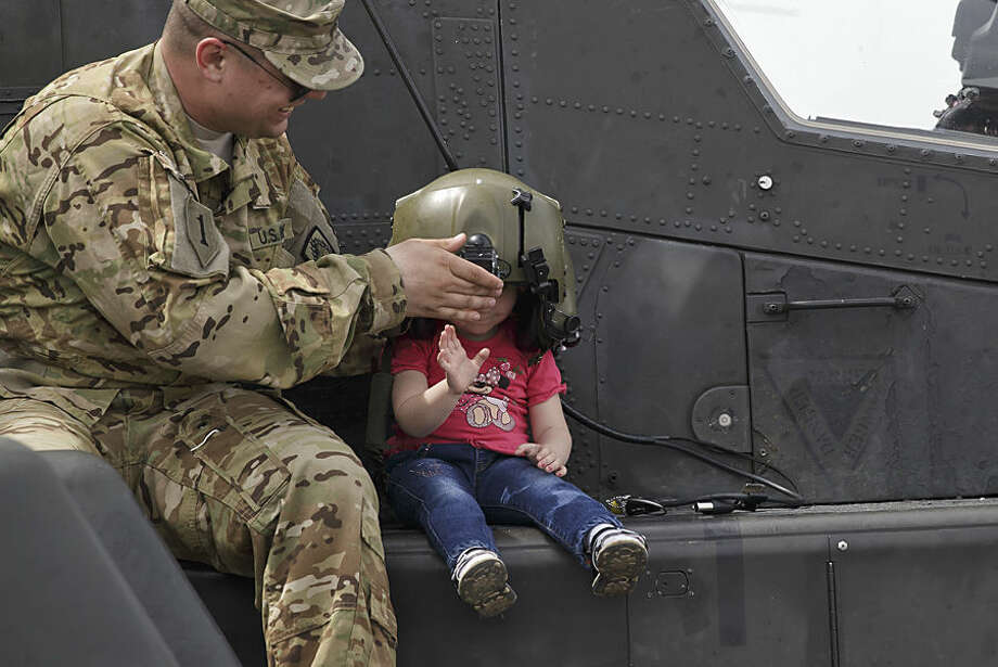 A US serviceman holds a pilot helmet for child posing on an Apache attack helicopter in Ploiesti, Romania, Wednesday, May 13, 2015. Members of the US military took part in an exercise dubbed the Cavalry March, a drive from southern Romania to a training range in the central region of Transylvania, involving 400 servicemen and 80 armored combat vehicles.(AP Photo/Vadim Ghirda)