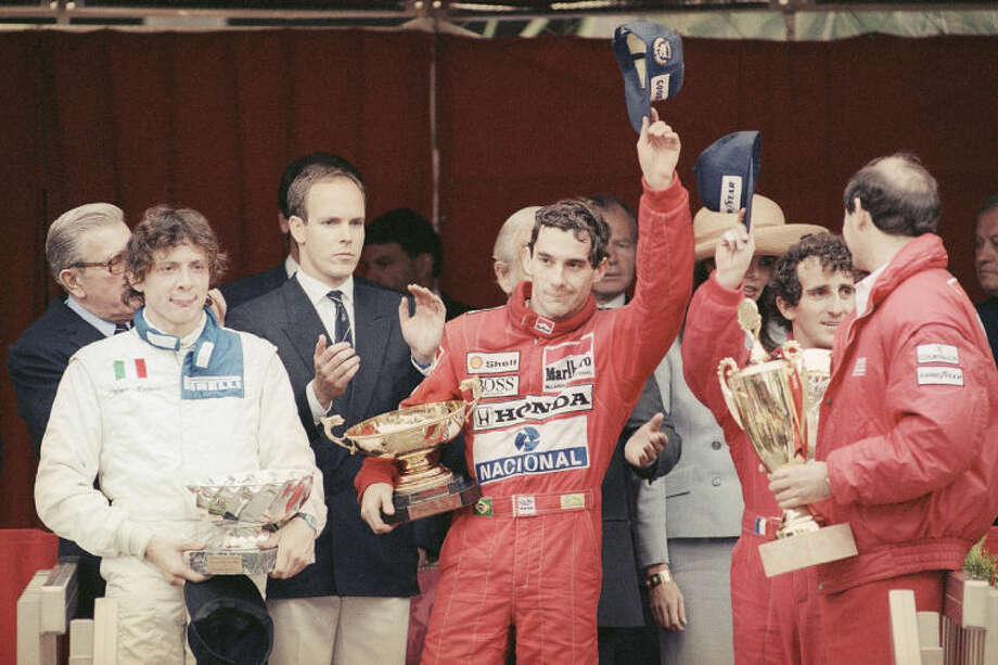FILE - In this May 7, 1989 file photo, Prince Albert of Monaco, left, applauds Brazil's Ayrton Senna, center, winner of the Monaco formula One grand prix ahead of Prost, right, on the podium in Monaco. Despite his career being cut short when he was 34, his 41 wins stand third all-time behind Michael Schumacher's 91 and rival Alain Prost's 51. He died at the 1994 San Marino Grand Prix. (AP Photo/Gilbert Tourte, File)