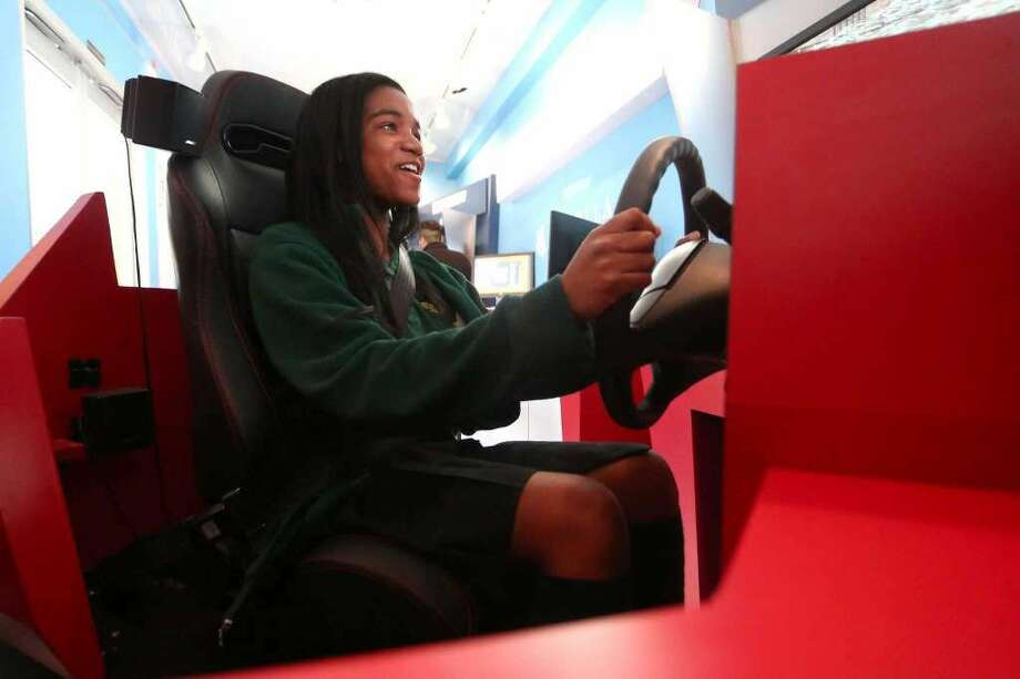16-year old Chelsey Gabriel, a sophomore at Trinity Catholic High School, smiles nervously while carefully driving the distracted driving training mobile parked outside of the school on Thursday, May 5, 2016. The simulator is meant to test new drivers in a variety of road scenarios, including crossing pedestrians and blind curves. (Photo: Michael Cummo / Hearst Connecticut Media)