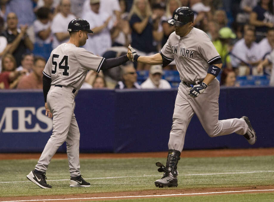 New York Yankees third base coach Joe Espada, left, congratulates Carlos Beltran after his solo home run off Tampa Bay Rays starter Alex Colome during the fifth inning of a baseball game Monday, May 11, 2015, in St. Petersburg, Fla. (AP Photo/Steve Nesius)