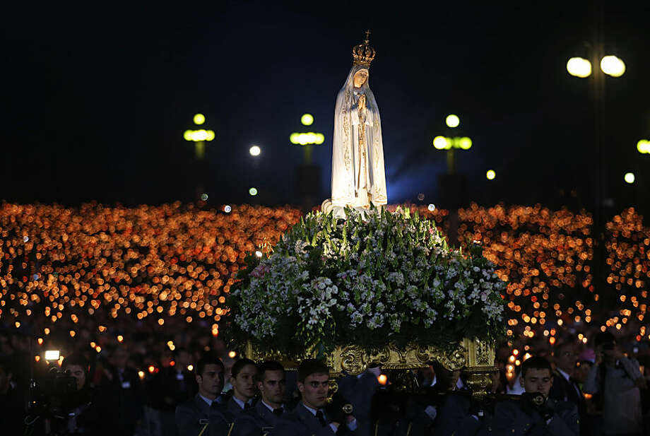A statue of Our Lady of Fatima is carried during a candle light vigil at the Our Lady of Fatima shrine, in Fatima, central Portugal, Tuesday, May 12, 2015. Every year on May 12 and 13, tens of thousands of Catholic believers go on pilgrimage to the Fatima's sanctuary to pray and attend masses where the Virgin Mary is believed to be witnessed by three shepherds children Lucia, Jacinta and Francisco in 1917. (AP Photo/Francisco Seco)