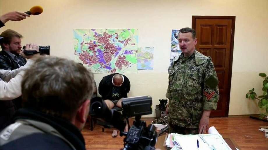 """This image taken from Associated Press video shows Igor Strelkov, military commander of pro-Russian militias in Slovyansk talking to journalists in Slovyansk, Ukraine, Sunday, April 27, 2014; in background, is one of three blindfolded and bound men who are allegedly the captured Ukrainian secret service members. Strelkov has been identified as a Russian security services operative by Ukraine's government. In what appeared to be a closely vetted interview to Russian media, Strelkov did not directly deny the accusation, saying the uprising in Ukraine was being carried out by opponents of the """"Kiev junta"""" — language similar in tone to that adopted by the Kremlin leadership. (AP Photo/Associated Press Video)"""
