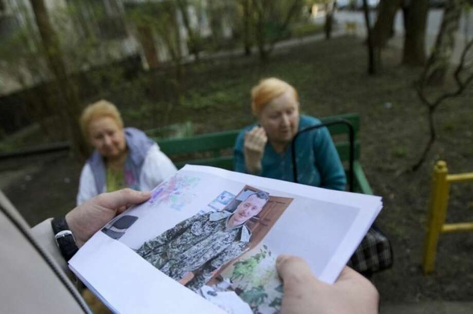 "A Ukrainian journalist shows a photograph of Igor Strelkov, a military commander of pro-Russian militias in Slovyansk, to his supposed neighbors in Moscow, Russia, Tuesday, April 29, 2014. Camera crews swarmed around an apartment building that Ukrainian TV reported to be home to the commander's mother. Neighbors told The Associated Press that a ""fancy black car"" had turned up Tuesday morning to whisk the woman away. Strelkov, speaking in Slovyansk, strengthened the case that Russia is behind the turmoil that is rocking the eastern part of the country. (AP Photo/Ivan Sekretarev)"