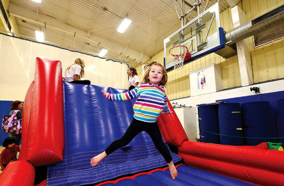 Hour photo / Erik Trautmann 3 year old Caroline Condon enjoys an inflatable attraction at the Wilton YMCA Healthy Kids Day Saturday.