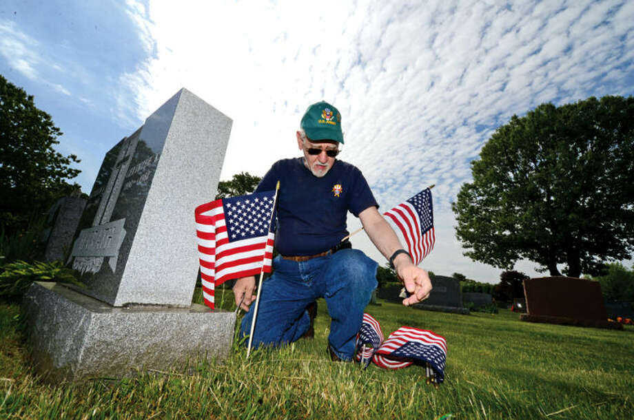 Airforce and Army veteran Frank Verdone honors fellow veterans as Northrop Grumman sponsors the placement of flags on the graves of veterans at St. Jonn's Cemetery last year. Hour photo / Erik Trautmann