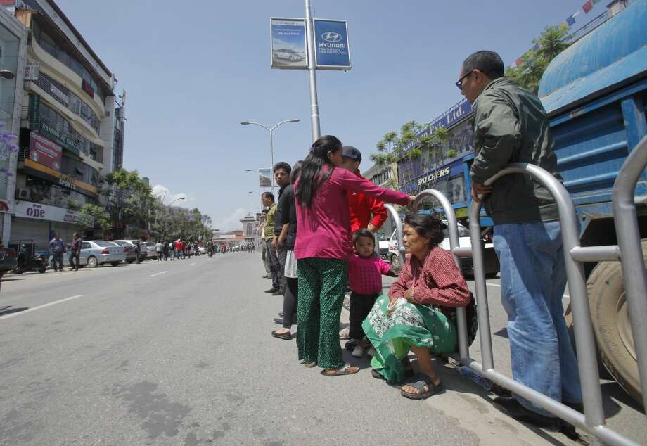 Nepalese people position themselves in the middle of a street for safety after an earthquake hit Nepal in Kathmandu, Nepal, Tuesday, May 12, 2015. A major earthquake hit a remote mountainous region of Nepal on Tuesday, triggering landslides and toppling buildings less than three weeks after the country was ravaged by another deadly quake. (AP Photo/Bikram Rai)