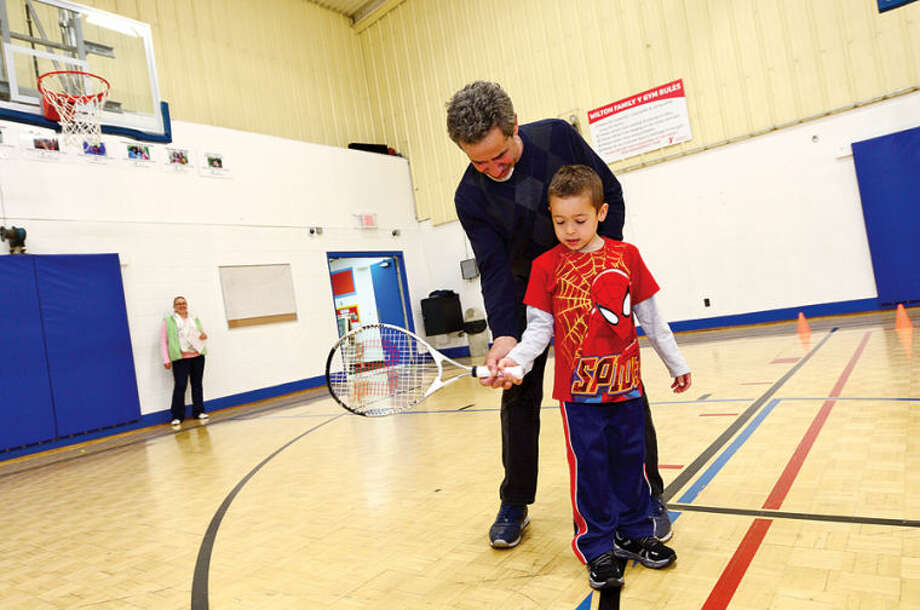 Hour photo / Erik Trautmann 5 year old Peter Braid gets help with his tennis swing from John Barbara of Fairfield County Tennis at the Wilton YMCA Healthy Kids Day Saturday.