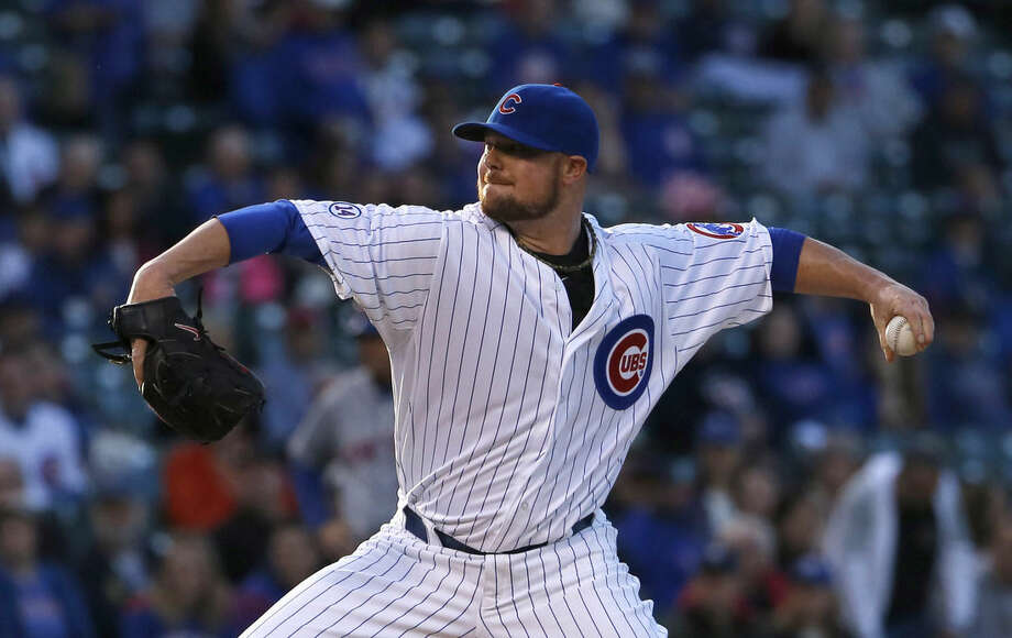 Chicago Cubs starting pitcher Jon Lester delivers in the setting sun during the first inning of a baseball game against the New York Mets Monday, May 11, 2015, in Chicago. (AP Photo/Charles Rex Arbogast)