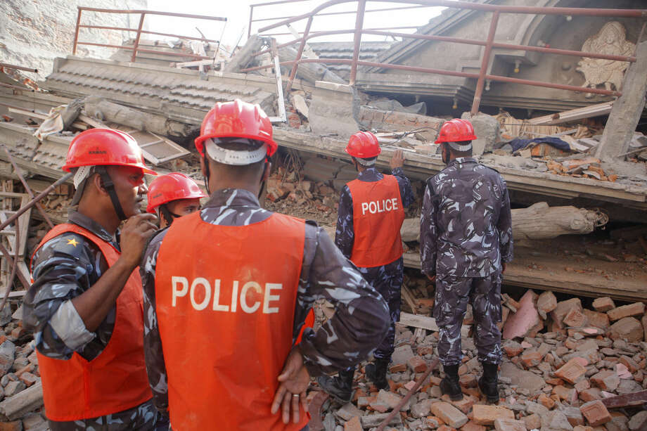 A Nepalese rescue team inspects the site of a building that collapsed in an earthquake in Kathmandu, Nepal, Tuesday, May 12, 2015. A major earthquake has hit Nepal near the Chinese border between the capital of Kathmandu and Mount Everest less than three weeks after the country was devastated by a quake. (AP Photo/Niranjan Shrestha)