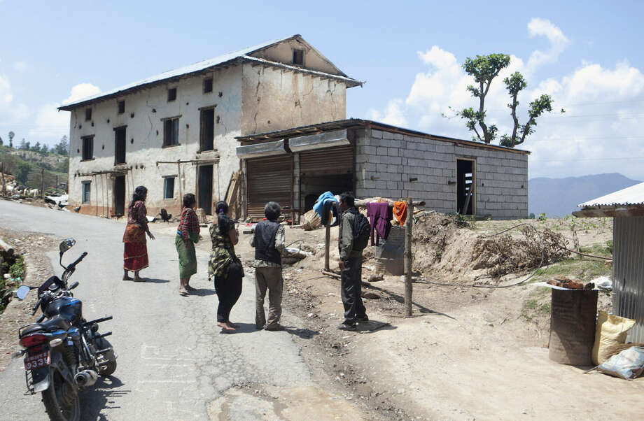 Nepalese people look at their shaking house after running out of it during an earthquake, on the outskirts of Kathmandu, Nepal, Tuesday, May 12, 2015. A major earthquake has hit Nepal near the Chinese border between the capital of Kathmandu and Mount Everest less than three weeks after the country was devastated by a quake. (AP Photo/Niranjan Shrestha)