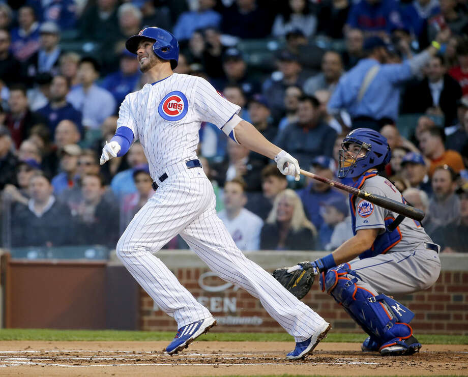 Chicago Cubs' Kris Bryant hits a two-run home run off New York Mets starting pitcher Jacob deGrom, Bryant's first home run in Wrigley Field, also scoring Dexter Fowler, during the first inning of a baseball game Monday, May 11, 2015, in Chicago. Also watching the play is catcher Kevin Plawecki. (AP Photo/Charles Rex Arbogast)