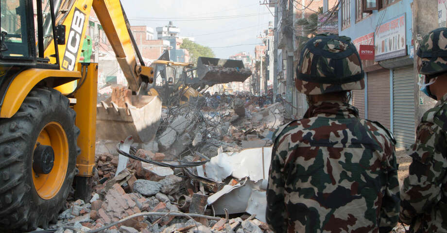 Earthmovers clear debris from the site of a building that collapsed in an earthquake in Kathmandu, Nepal, Tuesday, May 12, 2015. A major earthquake has hit Nepal near the Chinese border between the capital of Kathmandu and Mount Everest less than three weeks after the country was devastated by a quake. (AP Photo/Ranup Shrestha)