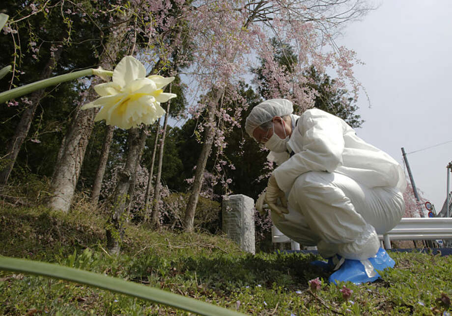 In this photo taken Thursday, April 17, 2014, Kazuhiro Onuki wearing a white protective gear and a mask measures the radiation level of the ground in Tomioka, Fukushima Prefecture, northeastern Japan. There is no running water or electricity. Above all, radiation is everywhere. It's difficult to imagine ever living again in Tomioka, a ghost town about 10 kilometers (6 miles) from the former Fukushima Dai-ichi nuclear plant. And yet. More than three years after meltdowns at the plant forced this community of 16,000 people to flee, Onuki can't quite make the psychological break to start anew. (AP Photo/Shizuo Kambayashi)
