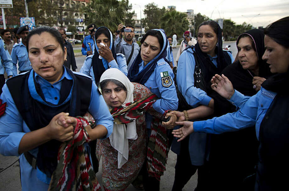 Pakistani police officers escort Amina Janjua, the wife of a missing person and rights activist in Islamabad, Pakistan, Monday, April, 28, 2014. Family members and human rights activists held a protest to demand information from the government about missing people who were reportedly picked up by security agencies during anti al-Qaida raids. (AP Photo/B.K. Bangash)