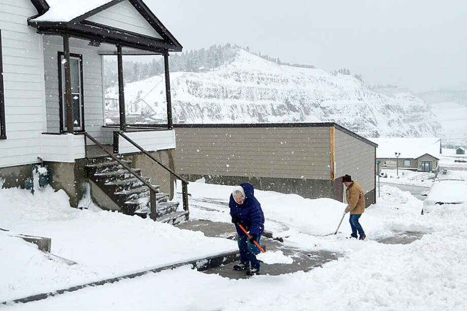 Donna Newlon, left, and her son, Lonny, clear their sidewalks Monday morning, April 28, 2014, at their home overlooking the Homestake Open Cut in Lead, S.D. A system that brought deadly weather to the central and southern U.S. over the weekend dumped heavy snow in western South Dakota late Sunday and early Monday. (AP Photo/Rapid City Journal, Tom Griffith)