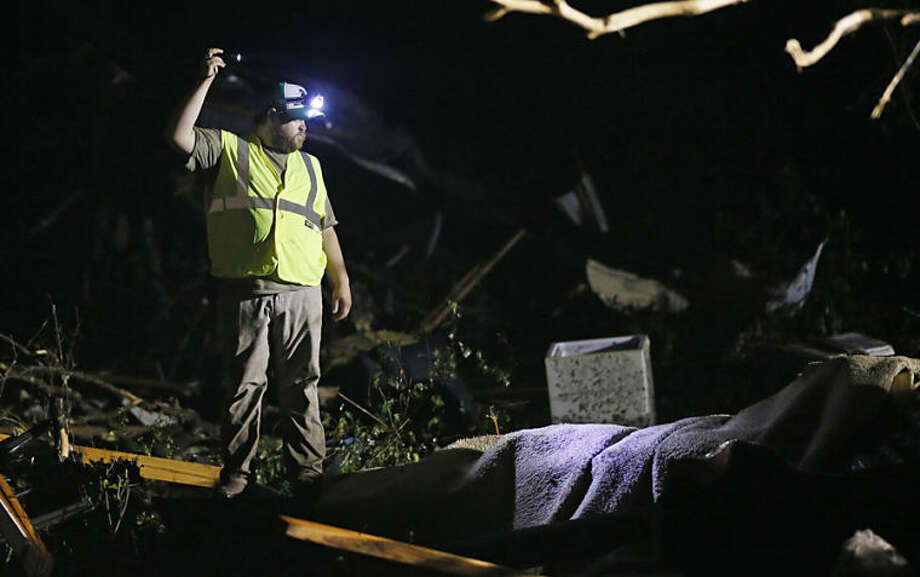 A responder shines his flashlight into the remains of several mobile homes as he searches for survivors in Louisville, Miss., early Tuesday morning, April 29, 2014 after a tornado hit the east Mississippi community Monday. Tornadoes flattened homes and businesses, flipped trucks over on highways and bent telephone poles into 45-degree angles as they barreled through Alabama and Mississippi on Monday, part of a storm system that killed at least nine people in the South and brought the overall death toll from two days of severe weather in the country to at least 26. (AP Photo/Rogelio V. Solis)